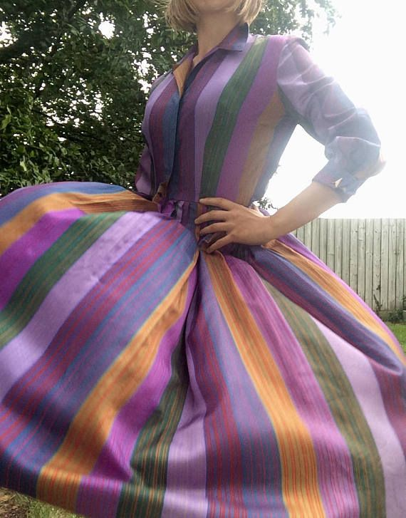 Stunning vintage 1960s purple multi coloured striped dress  Gorgeous / divine dress  3/4 length sleeves, which have their own arrow head cuff links to join the cuffs. Shine like material  Metal zip at the rear  Size 8, possible small 10, please see measurements Pit to pit- 17 inches  Waist- 13.5 inches  Length- 44 inches  Overall in good vintage condition, couple of minor issues. Very small under 1cm rip at bottom of skirt area, hard to notice. Loose threading just above waist area....