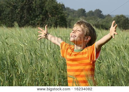 happy christian child arms raised in happiness and faith | Stock photo