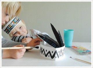 Adhiere las plumas a la banda. En la imagen vemos a un niño decorando un segundo diseño, mucho más sencillo.