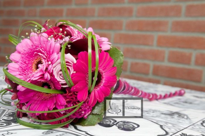 Roze boeket met roosjes, germini's, celosia, gipskruid en afgewerkt met beregras en galaxblad. De steel is op een bijzondere manier afgewerkt.