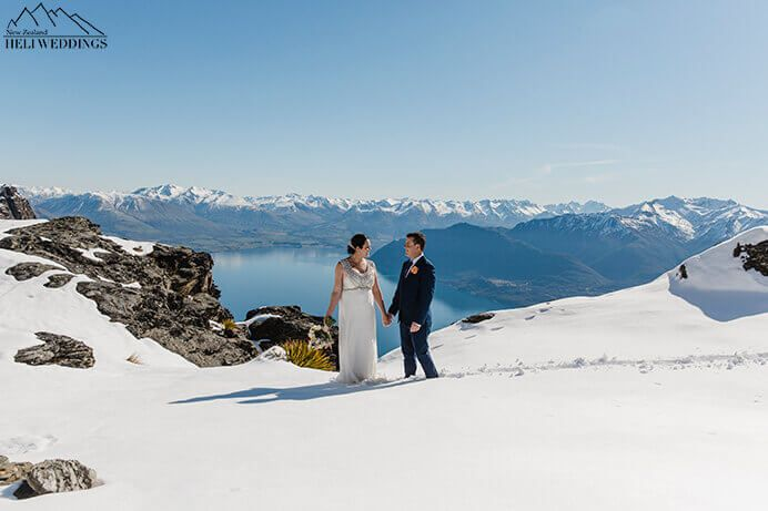 Bride and groom stand in snow on sunny spring day. The Ledge Destination Heli weddings Queenstown.