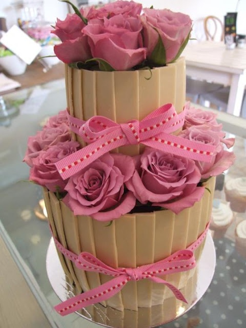 Beautiful vanilla cake with vanilla butter frosting, white chocolate collar and rose detail.