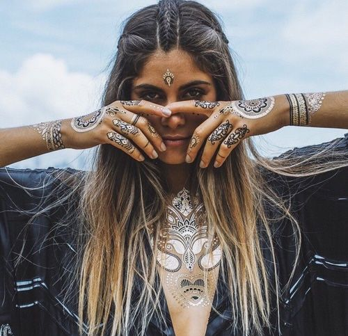 adornment. artist ? material; gold and black body tattoos