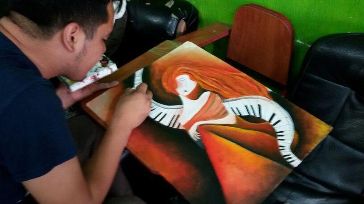 Carlos Garay pinting at his brother Juan's Barber shop in San Jose Pinula, Guatemala