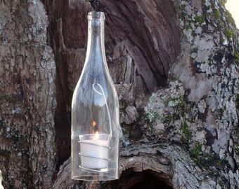 Wijnfles opknoping lantaarns.  Romantische verlichting voor indoor of outdoor.  Set van 3 lantaarns.  Groen, goud en olijf bruin glazen 750 ml. wijn flessen.  Vlam knippen en minutieus hand geschuurd in een 3-stap proces voor een perfect glad en schuine rand.  Hand vervaardigde inzetprijzen draad houdt een votief glas. Solide metalen hals ring leidt tot zwarte metalen keten die is bekroond met een grotere metalen lus link voor gemakkelijk opknoping.  Hangende ketens zijn in 3 verschillende…