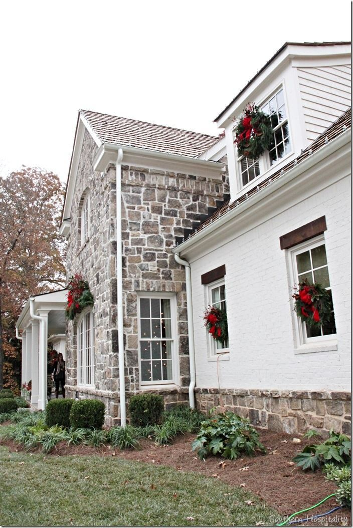 Stone wreath flanked windows of beautiful stone exterior home