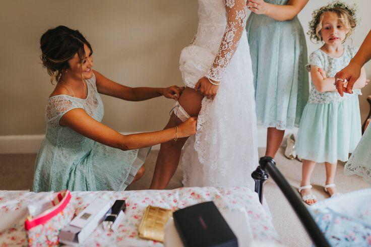 This flower girl's reaction to the garter is priceless! Photo by Benjamin Stuart Photography #weddingphotography #garter #flowergirl #bridesmaids #bride #weddingday #bridalprep