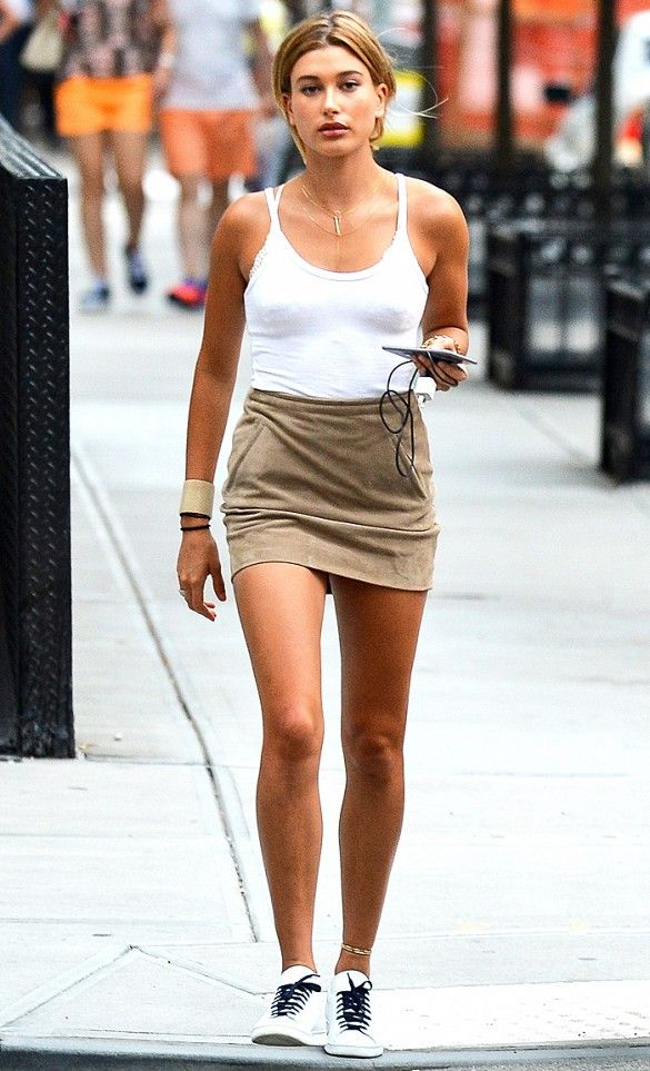 Hailey Baldwin wears a white tank top with a suede miniskirt, white sneakers, and a gold anklet