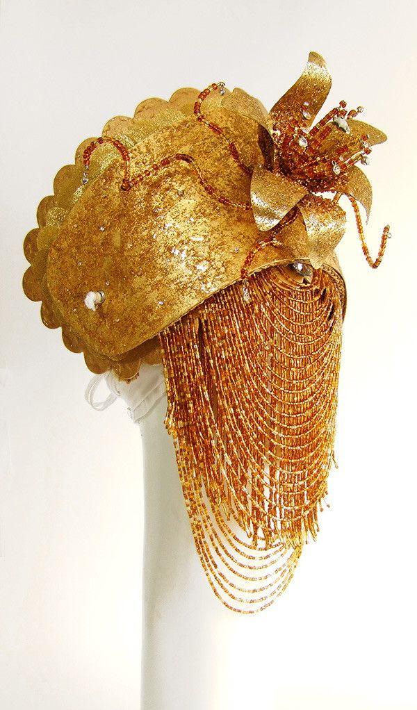 Conjunto de paramentos para Kisimbi, formado por adê, abebê, impulsas de braço e pulso e cinturão. Confeccionados em latão moldado e pintura artística dourada. Acabamentos em cristais, muranos, miçangas, pingentes de metal e vidrilhos.