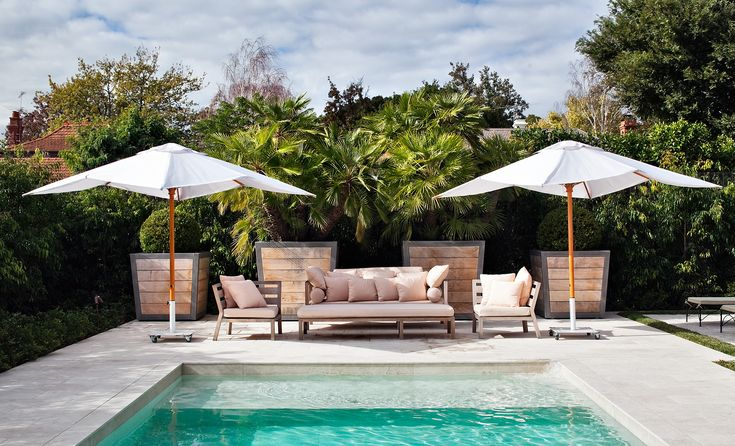 Large scale timber Hamptons Pots with Buxus microphylla spheres. Travertine pavers around pool area. Armadale, Victoria Australia Anthony Wyer + Associates http://www.anthonywyer.com