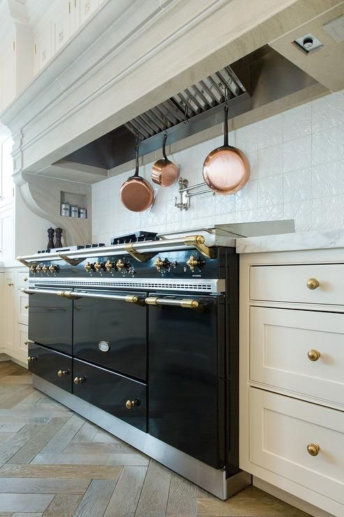 Flanked by white shaker cabinets finished with brass pulls, a black Lacanche range is sat against white glazed backsplash tiles framing a pot rack mounted to the underside of a wood kitchen hood in this well appointed transitional kitchen.