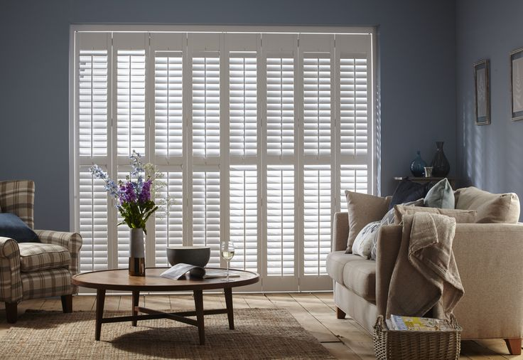 White Full Height Lounge Shutters by Apollo Blinds. White and blue home decor inspiration. Modern window dressing. Living room shutters.
