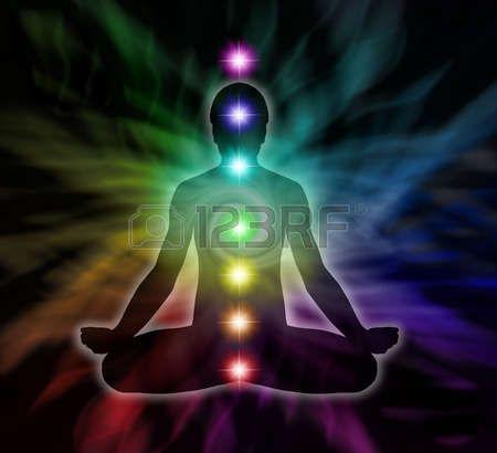 energia espiritual: Silouette de un hombre en posición de loto meditación con siete Chakras fluye sobre fondo arco iris de energía