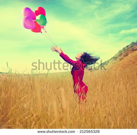 a girl walking in a field letting go of a bunch of balloons done with a vintage…