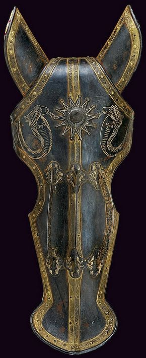 Indo-Persian chamfron (armor for a horses head), 19th Century, blued iron, with a cusp and three arched mounts, the border decorated by a gilt plaque engraved with floral motifs, at the upper part two gold-inlaid engravings depicting cobras; with ear covers, complete with inside stuffing, 68 cm.