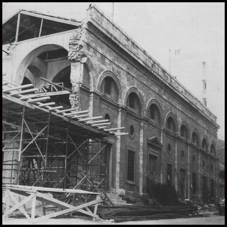 """Οι Αποθήκες του Πειραιά στη συμβολή των οδών Ευπλοίας και Αγίου Νικολάου την δεκαετία του 1970. Η αρχιτεκτονική του κτιρίου αποδίδεται στον Σταμάτη Κλεάνθη. Φωτογραφία από το βιβλίο του Στέλιου Β. Σκοπελίτη """"Νεοκλασικά σπίτια της Αθήνας και του Πειραιά""""."""
