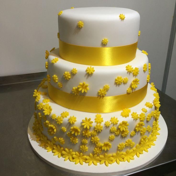 Třípatrový svatební dort obalený fondánem, dozdobený saténovou stuhou a žlutými fondánovými kytičkami.