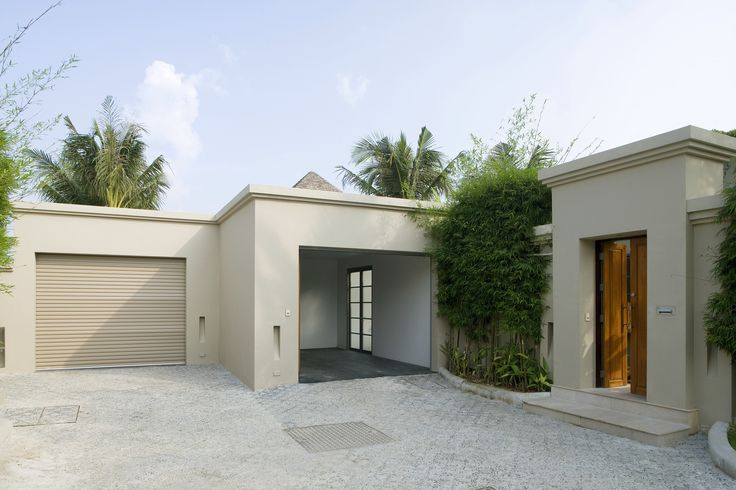 A modern ranch style home with white stucco siding. The