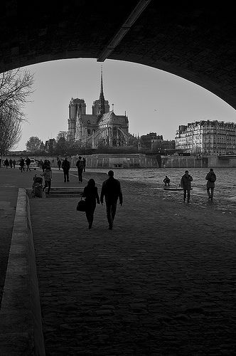 Notre Dame, Paris. A couple walks under a bridge on the banks of the