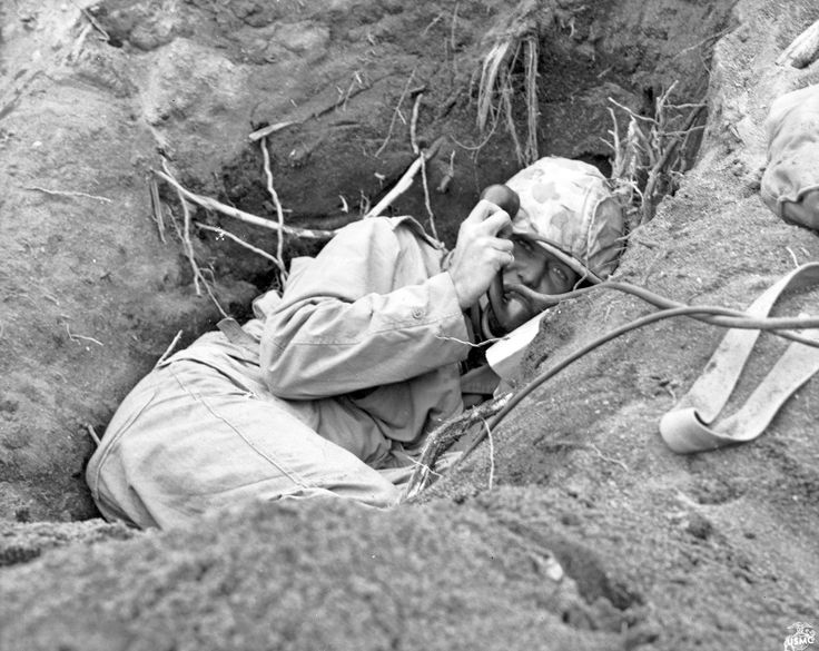 Striking images from the battle of Iwo Jima: A U.S. Marine communicator, burrowed in a shallow foxhole, calling for artillery support to silence enemy mortars in Iwo Jima.