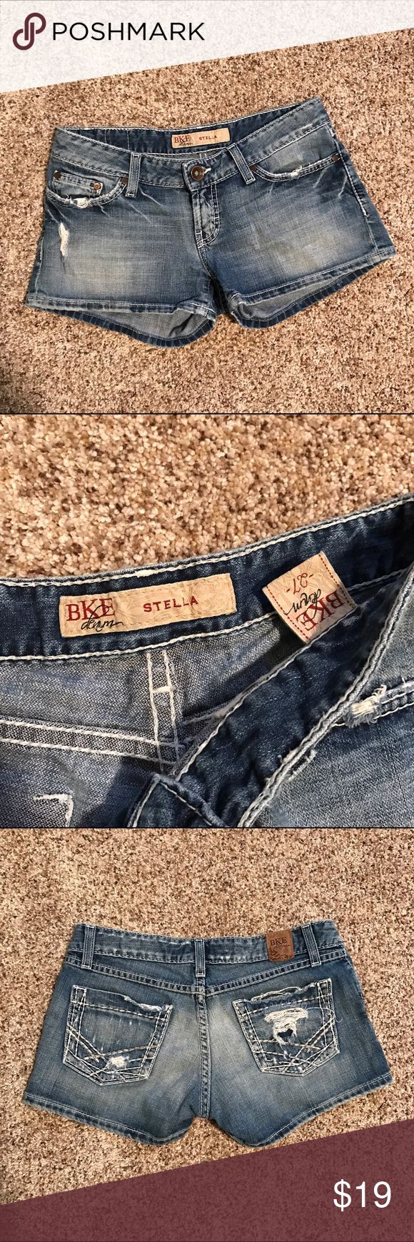 """BKE Stella Blue Jean Shorts size 27 BKE Stella Distressed Blue Jean Shorts. Purchased from Buckle. Size 27. Waist laying flat 15 1/2"""", waist around 33 1/2"""", inseam 2 1/2"""". Factory fraying, fading, rips, tears and/or holes for distressed look. In very good condition, worn 3-4 times. BKE Shorts Jean Shorts"""