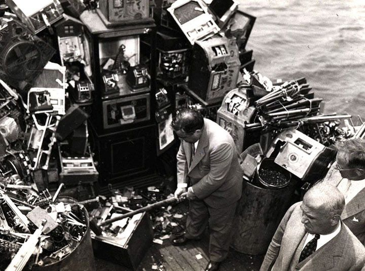 Aboard a police boat on October 10, 1934, New York Mayor Fiorello LaGuardia hacks away at confiscated slot machines about to be destroyed and dumped into New York harbor. (Courtesy NYC Municipal Archives) #