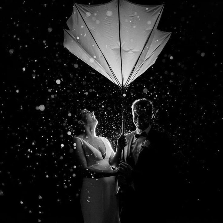 One of the most stunning shots we have seen! AV Bride Karrisa and her groom, Michael, letting it rain on their parade, but smiles all around! This rainy night shot was captured by Sarah Godenzi Photography