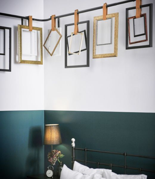 Different types of frames are hung from an IKEA HUGAD curtain rod with leather straps (buy some leather at fabric store, cut strips into different lengths, attach snaps).