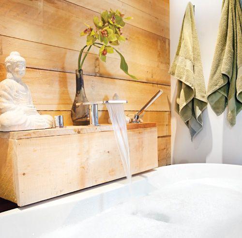 Grand amateur de surf, le propriétaire de cette salle de bainsouhaitait créer une ambiance zen et exotique à la façon balinaise.La présence de noir du plancher au plafond et l'intégrationde matières naturelles, comme le mur en planches de pinet le dosseret de pierres, évoquent le calme et la spiritualité.