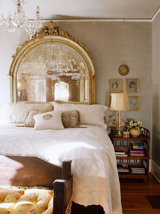 """Headstrong Architectural relics, such as this dramatic old bar mirror, make great impromptu headboards. The oversize scale of the piece works in this master bedroom because the mirror reflects so much light, giving the appearance of spaciousness. White matelasse linens add interesting texture while allowing the mirror to shine."""