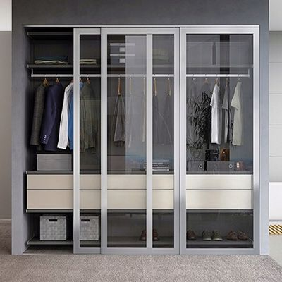 Elegant sliding glass doors give this well-designed storage solution an added hint of chic. © California Closets