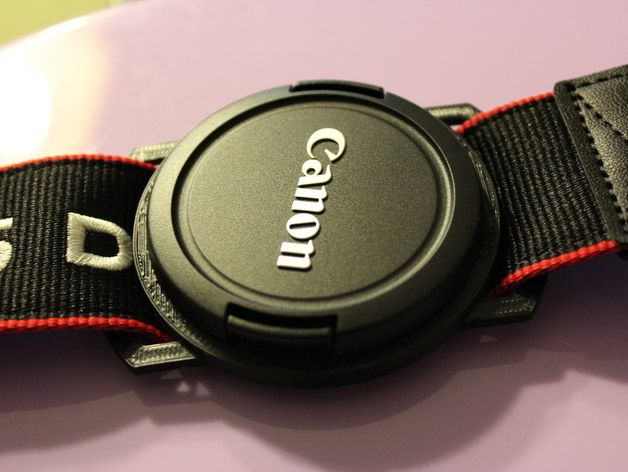 A (parametric) buckle that you can attach to your camera strap, which lets you (hopefully) stop losing your lens cap. The STL is sized for a 58mm lens cap, and a ~40mm strap width. The printing layers make for a great friction catch for the lens cap.  But there's a designed-in lip overhang to make it a little more aggressive.