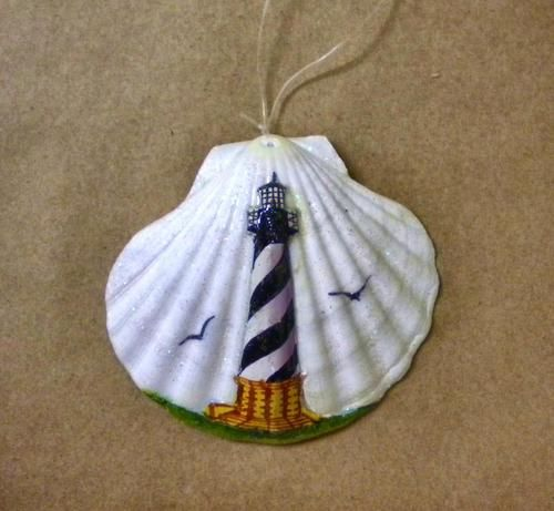 "Very attractive lighthouse scene painted on a 4 1/2"" clam shell. With two birds flying and a hint of glitter, this ornament will add some sparkle to your Christmas tree."