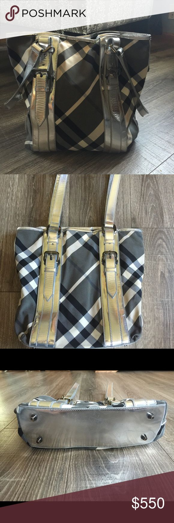 Authentic Burberry Beat Check Victoria Tote Bag Add add a hint of luxe to your weekend casual look! Original retail $800+ hard to find in silver!! - Beat check nylon body with patent leather trim - Gunmetal tone hardware - Double top handles - Magnetic snap tab closure - 4 protective metal feet - Fabric lining - 1 zipper pocket, 2 slip pockets - Debossed designer label  - Discolouration and stains on fabric body  - Scratches on protective metal feet and leather  Measurement: Length (at base)…