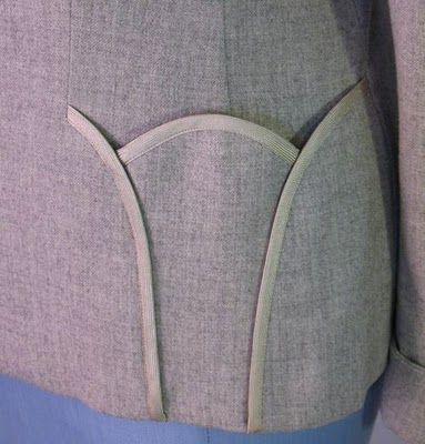 The pockets of this 1950s Lilli Ann suit jacket are made of 3 sections that are edged with braid.