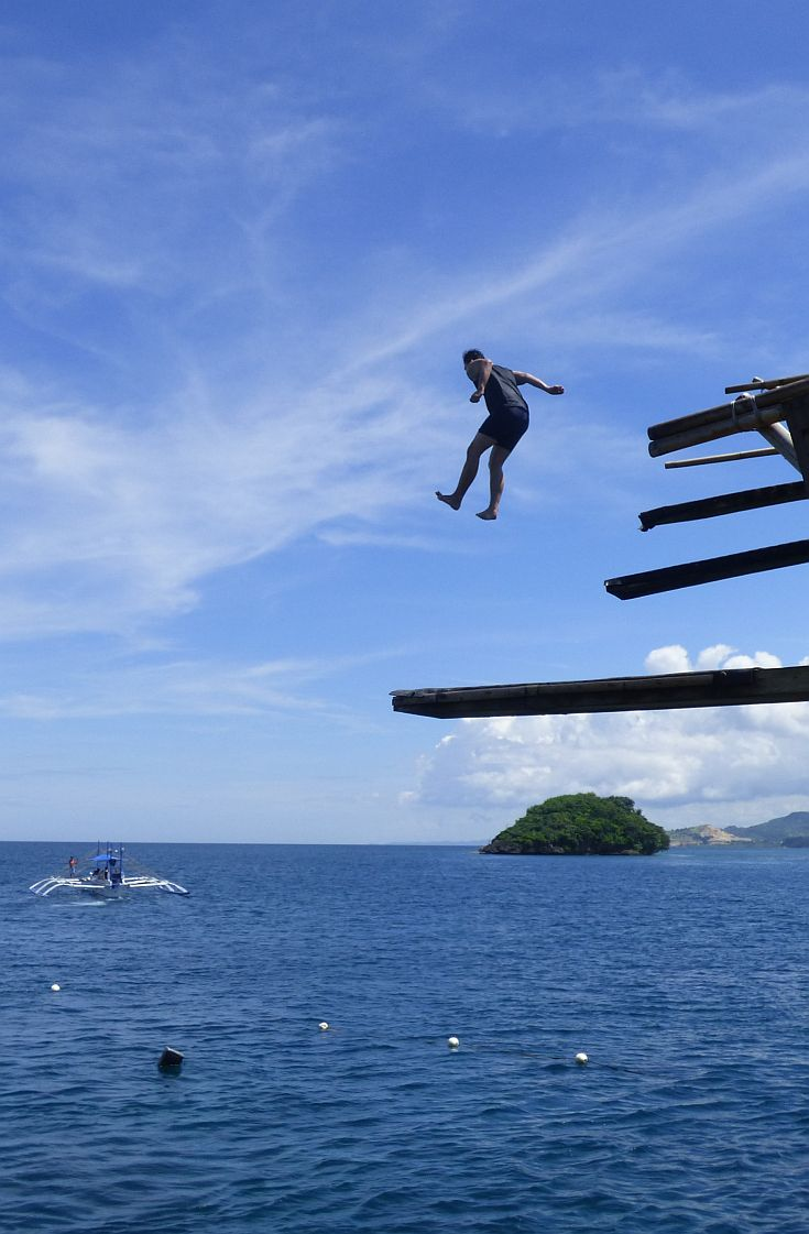 Guy jumping into the sea in Boracay - Philippines. From the article On a Blowout Budget in Boracay in Perceptive Travel.