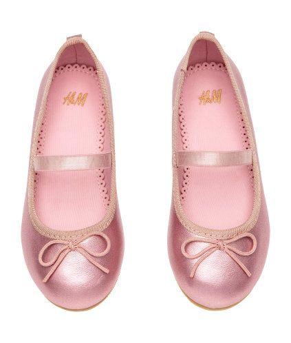 Rosa/Metallic. Ett par ballerinaskor med resår över foten och dekorativ rosett fram. De har ripsband kring ovankanten och hälla bak. Foder och innersula i