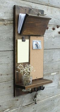 please allow 2-3 weeks for completion. thanks  Mail holder is fully adjustable and ties with heavy jute cord. Large enough for those little over sized pieces of mail  Cork board measures approx. 12 x 7 with decorative black screws. Note pad is 6 x 4 and hangs from a rustic metal clip. **** Note pads will now be solid white not the yellow lined.  Mason jar shelf measures 11 x 3.5 and jar is easily removable and included.  Stained in Dark Walnut and lightly distressed. Finished with a quality…