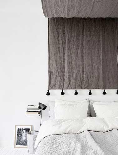 Ici, un drapé en lin couleur taupe utilisé en ciel de lit est descendu jusqu'au dessus des oreillers pour faire la tête de lit dans un esprit ethnique. Voilà une belle idée pour fabriquer en un tour de main une tête de lit originale ! A refaire très simplement avec un beau tissu uni comme dans cette exemple pour réveiller une déco de chambre blanche. Le plus déco, choisir un tissu à motifs colorés pour créer une chambre à l'allure baroque.