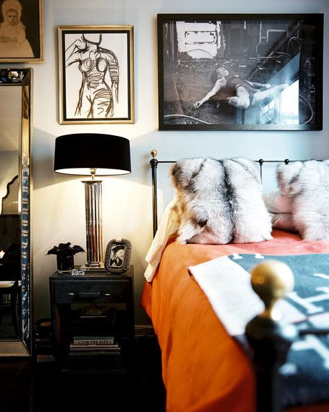 An orange quilt adds a pop of color to this otherwise black-and-white bedroom designed by Ryan Korban. | Lonny.com