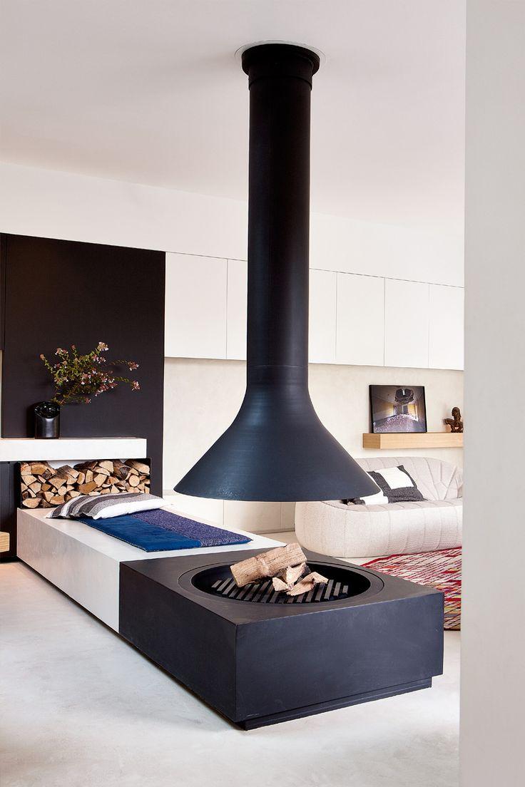 Una gran chimenea de hierro de diseño contemporáneo preside el espacio central.