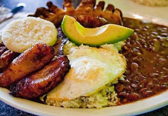 Bandeja Paisa. Is a typical meal popular in Colombian cuisine, especially of the Antioquia department and the Paisa Region. The main characteristic of this dish is the generous amount and variety of food in a traditional bandeja paisa: red beans cooked with pork, white rice, ground meat, chicharon, fried egg, plantain (patacones), chorizo, arepa, hogao sauce, black pudding (morcilla), avocado and lemon.
