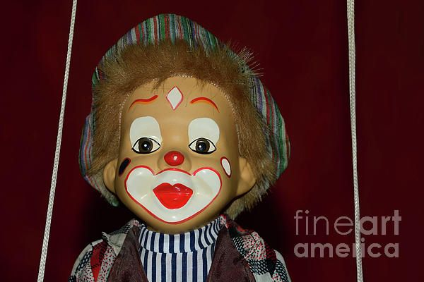 A cute little clown with a brightly painted face sitting on a swing, hence the ropes on side. Stripes and ragged clothes. Cute Little Clown by Kaye Menner Photography Quality Prints Cards Products at: https://kaye-menner.pixels.com/featured/cute-little-clown-by-kaye-menner-kaye-menner.html
