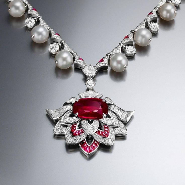BULGARI -  Festa Cuore di Roma Mozambique Ruby Necklace - From iconic Italian jeweller Bulgari's Festa high jewellery collection, which was inspired by celebrations and parties of all natures. A 12.10-carat Mozambique oval Ruby flanked by Diamonds represents the Cuore or heart of Rome in a necklace further adorned with 17 Akoya Pearls. An additional 4.03 carats of buff-top Rubies adorn the necklace. Set in Platinum.