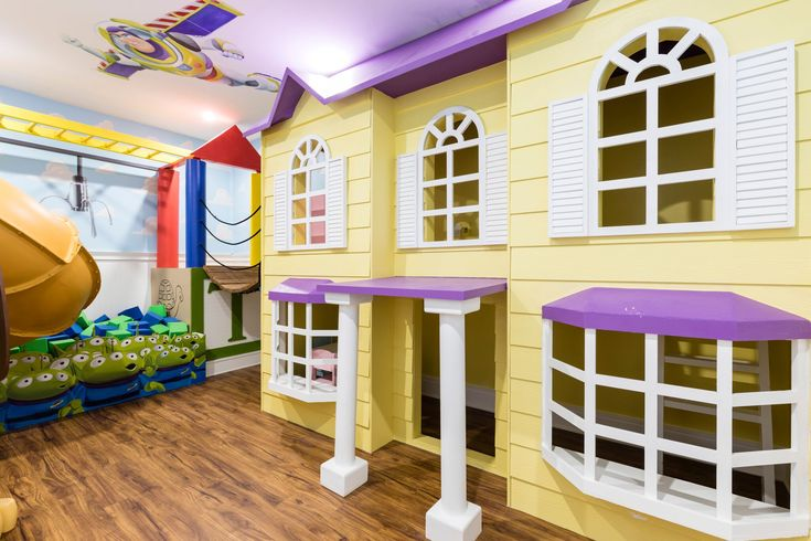 This Toy Story themed room is magical . It features a life size doll house and slinky slide . #toystory #suzannenicholsdesigngroup #playroom #slide