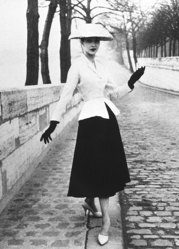 """Este visual tem como nome """"Bar Suit"""", sendo o grande icón do """"New Look"""" de Dior, que exibia delicadamente o corpo feminino. Designava-se por um pequeno chapéu, luvas, sapatos, por uma saia plissada (que deveria estar obrigatoriamente 40 cm do chão) e por uma jaqueta que seria o toque perfeito de uma estrutura que garantia uma aparência de elegância."""