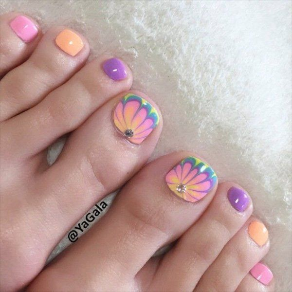 A cute baby colored daisy inspired toenail art design. If you are into baby colors and flowers then this is the perfect toenail art for you! Start out with a variety of baby colors as base and highlight daisy petals on the big toenail whilst topping the design with a silver bead.