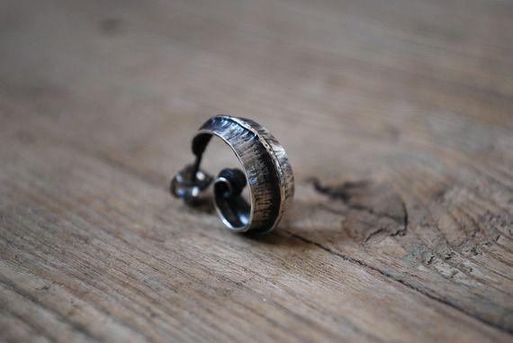 Une boucle d'oreille solitaire forgée en argent massif patiné pour homme ou femme