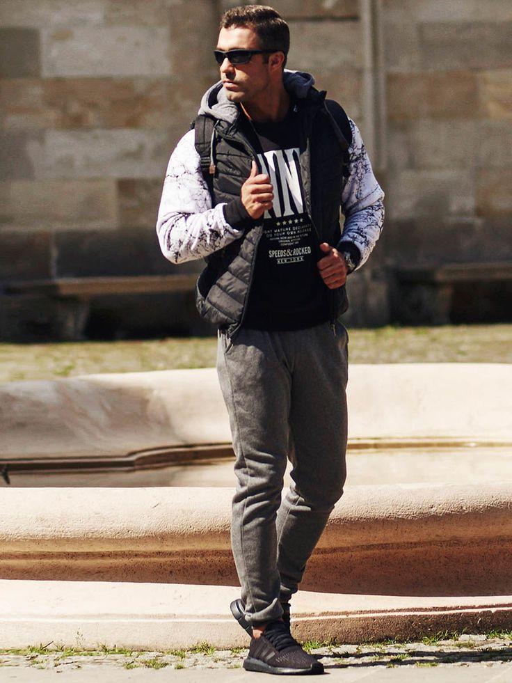 Sportowo-streetowa stylizacja na kapryśną pogodę. Grafitowe spodnie dresowe zestawiliśmy w niej z ciekawą bluzą z nadrukiem i reglanowymi rękawami. Do tego dodajemy świetny, pikowany bezrękawnik i okulary przeciwsłoneczne.