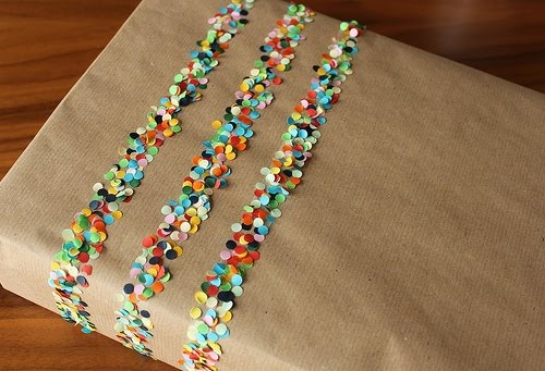Three strips of double sided sticky tape covered in bright colored confetti makes for fun and festive wrapping paper!